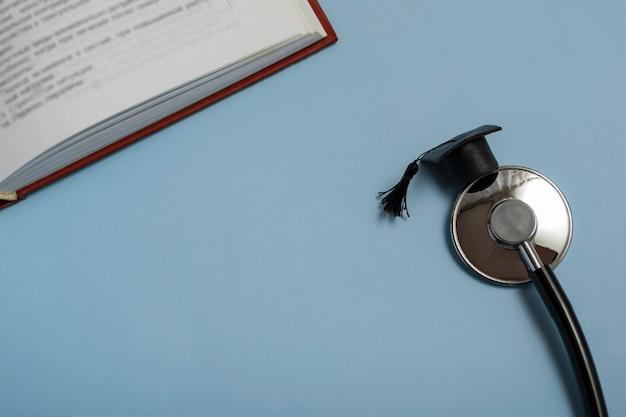 医学教育。聴診器、本、卒業式の帽子。青い背景の医療コンセプト。卒業