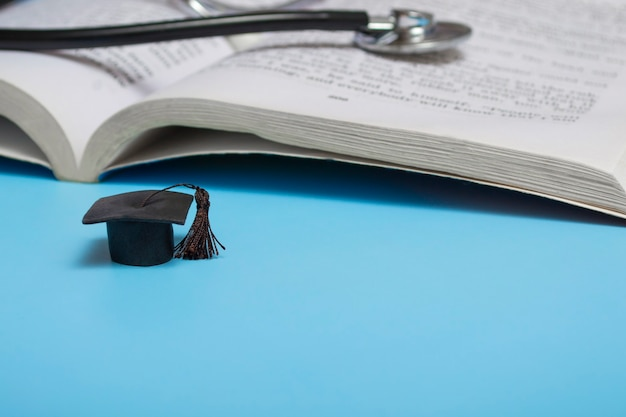 Medical education. stethoscope, book and graduate hat. medical concept on blue background. graduate