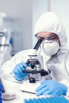 Инженер-медик настраивает микроскоп во время расследования коронавируса ученый в защитном костюме сидит на рабочем месте, используя современные медицинские технологии во время глобальной эпидемии.