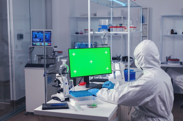 Medical engineer conducting research on computer with green screen during covornavirus
