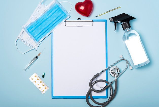 Medical equipment mockup clipboard, stethoscope with red heart and drug, surgical mask on blue copy space background.