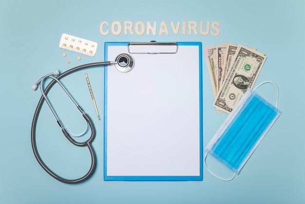 聴診器と薬物、青い背景にサージカルマスクと医療機器モックアップクリップボード。コロナウイルスの概念。
