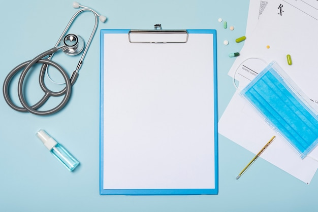 Medical equipment mockup clipboard with stethoscope and drug, surgical mask on blue copy space background.