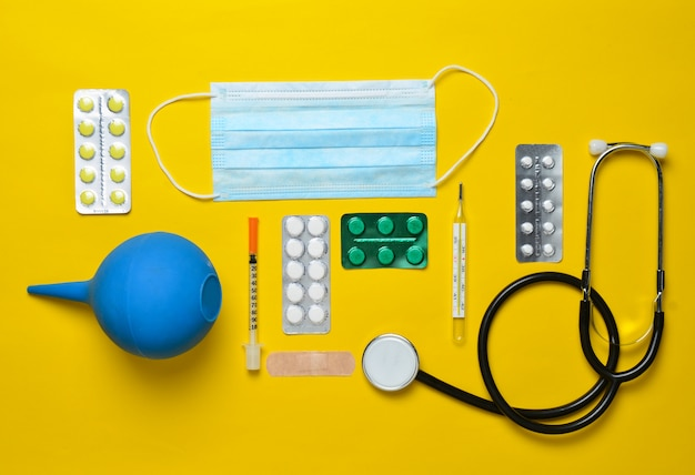 Medical equipment on a yellow background. enema, blisters pills, notebook, stethoscope, syringe, thermometer. medical concept, top view, flat lay style