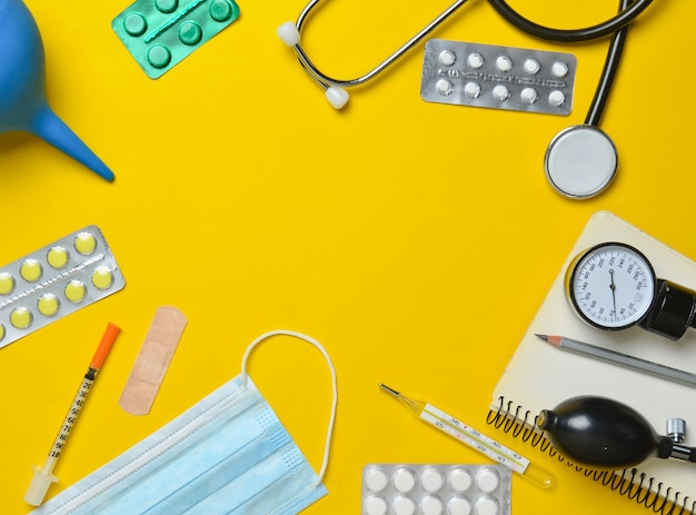Medical equipment on a yellow background. enema, blisters pills, notepad, stethoscope, syringe, thermometer, manometer. medical concept, top view, flat lay style, copy space