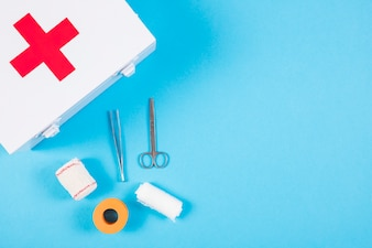 Medical equipments with first aid kit on blue background