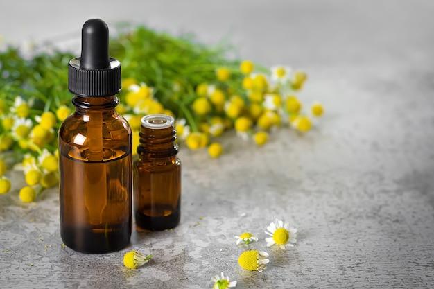 Бутылки с медицинским эфирным маслом и травы цветения ромашки на каменной поверхности