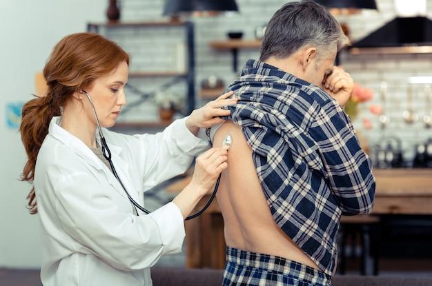 건강 검사. 그녀의 전문 청진기를 사용하는 동안 그녀의 환자 뒤에 서 좋은 심각한 의사