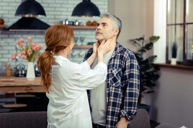건강 검사. 그를 검사하는 동안 그녀의 환자의 목을 만지고 전문 여성 의사