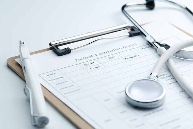 Medical examination report and stethoscope on white desktop