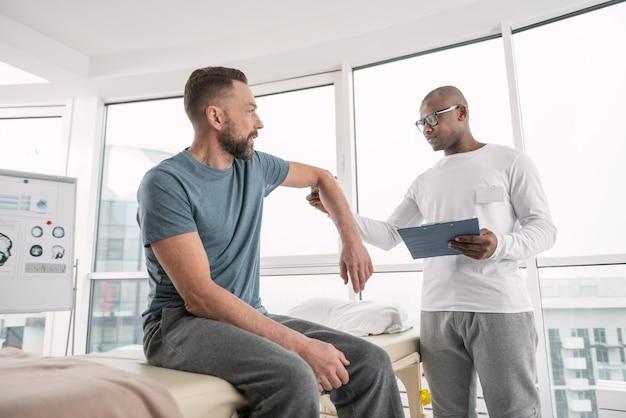 健康診断。それを調べている間彼の患者の腕を保持している深刻な素敵な専門の医者