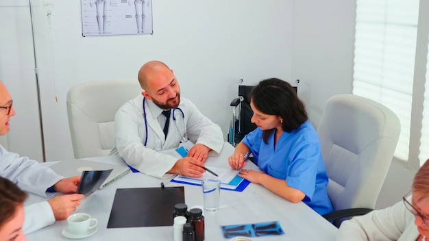 Медицинский эксперт разговаривает с медицинским персоналом во время встречи с медицинским персоналом в конференц-зале больницы, объясняя рентгенограммы. клинический терапевт разговаривает с коллегами о болезни, профессиональном медицине
