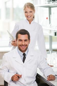 의료 전문가. 실험실에서 함께 일하는 동안 카메라를 보고 웃고 있는 두 명의 행복한 젊은 과학자