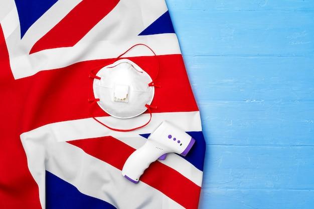 의료 얼굴 마스크 및 영국 국기, 코로나 바이러스 개념에 비접촉식 온도계