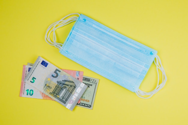 Медицинская маска для лица и деньги.