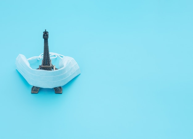 医療用フェイスマスクは、青い背景の旅行の魅力をカバーしています