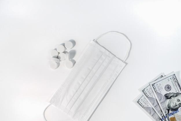 医療用フェイスマスク、お金と丸薬、白い背景で隔離