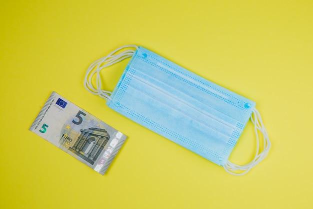 Medical face mask and money, world coronavirus epidemic and economic damages.