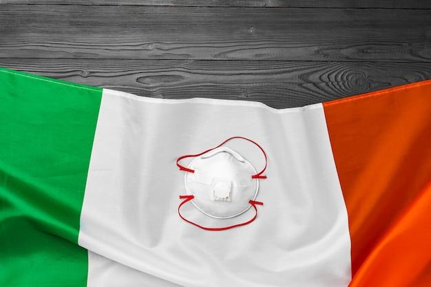 Медицинская маска для лица на флаге италии на деревянной доске