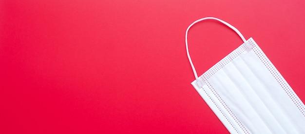 赤い背景の医療用フェイスマスクは、コロナウイルスまたはコロナウイルス病(covid-19)を防ぎます。