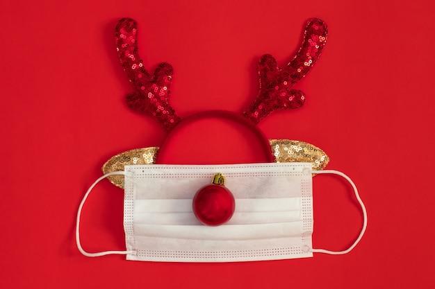 Медицинская маска для лица с рогами оленя на красном фоне. концепция рождества перед лицом пандемии covid-19.