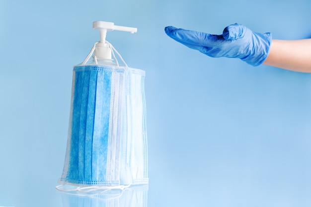Медицинские маски для лица, хирургическая защитная одноразовая маска на бутылочном спиртовом геле для дезинфекции рук врача в перчатках.
