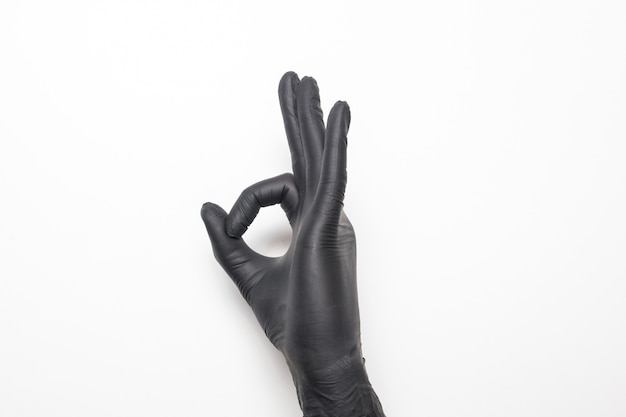 Medical glove in black on a white surface. hand showing okay sign.