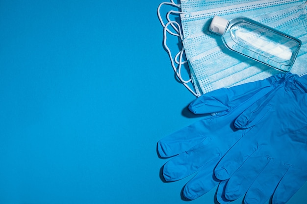 Маска медицинских перчаток и спиртовой гель для защиты от инфекции во время пандемии коронавируса, вид сверху на голубом фоне с копией пространства