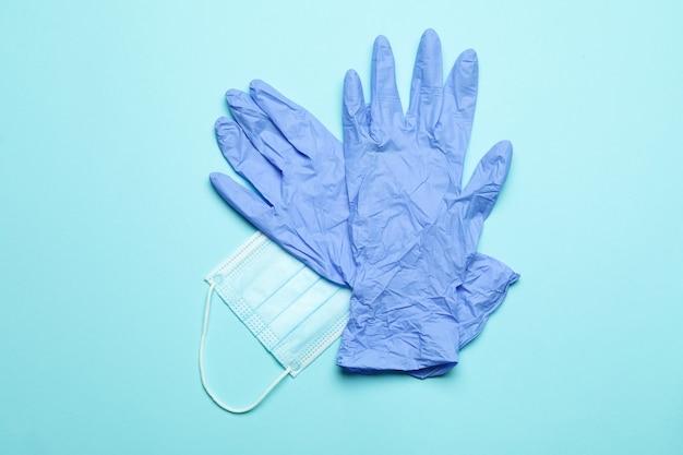 青のマスクが付いている医療用手袋