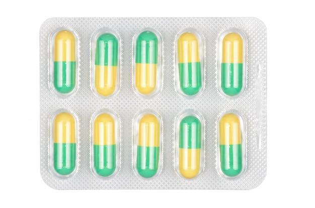 Медицинские зеленые и желтые таблетки в блистере на белом фоне