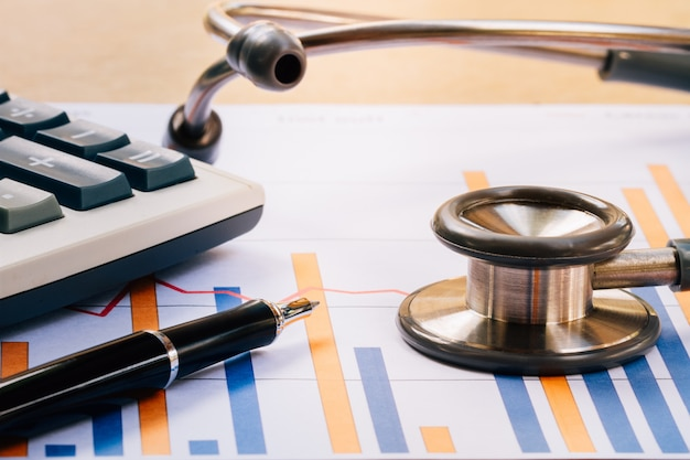 Medical headphones, stethoscope with financial report chart and calculator on desk