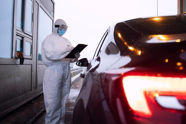 Медицинский работник в белом защитном костюме, контролирующий пассажиров и тест пцр при пересечении границы из-за глобальной пандемии вируса короны.