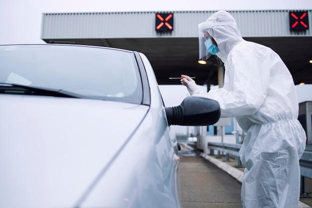 Медицинский работник в белом защитном костюме, перчатках и маске берет мазок из носа и горла для проверки пассажира на вирус короны.