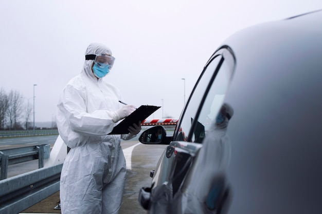 Medical heath care worker in protective white suit controlling passengers and pcr test at border crossing due to global corona virus pandemic.