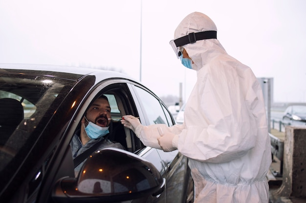 Medical heath care worker in protective white suit with gloves and face mask taking nasal and throat swab to test passenger for corona virus.