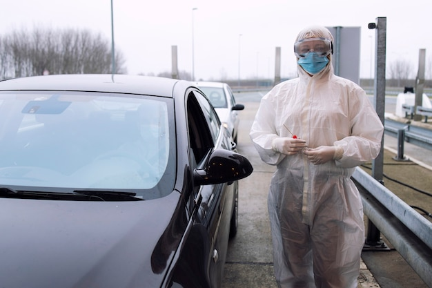 Medical heath care worker in protective white suit with gloves standing at border crossing and holding test kit for corona virus.