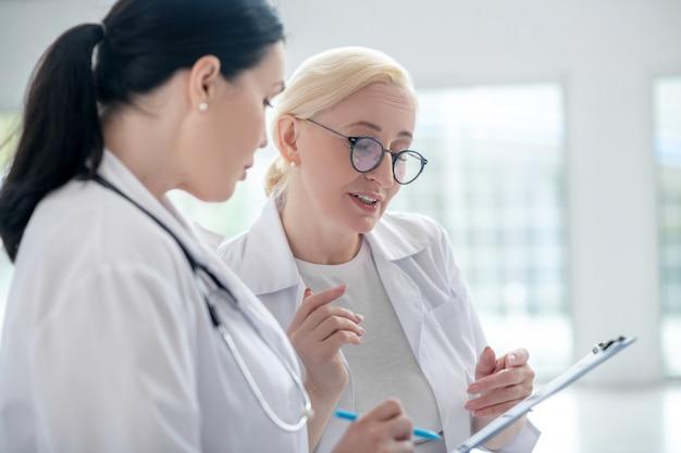 История болезни. две женщины-доктора читают историю болезни и выглядят вовлеченными