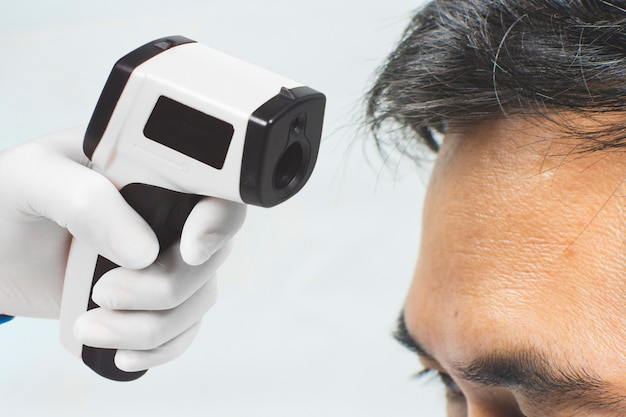 Medical infrared thermometer in a hand of the doctor measuring the temperature of the asian male patient.