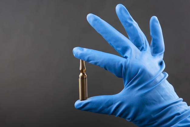 파란색 장갑을 낀 손에 의료 주입 용액