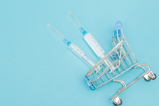 Medical injection in shopping trolley on blue background.