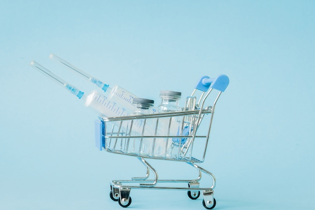 Medical injection in shopping trolley on blue wall. creative idea for health care cost, drugstore, health insurance and pharmaceutical company business concept. copy space