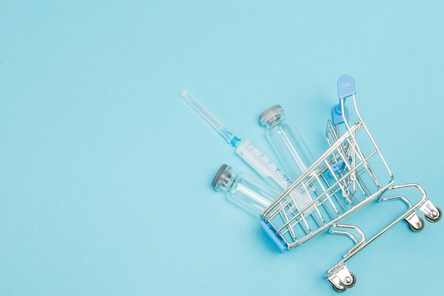 Medical injection in shopping trolley. creative idea for health care cost, drugstore, health insurance and pharmaceutical company business concept. copy space