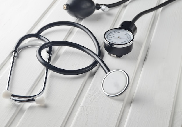 Medical instrument for measuring pressure. stethoscope on a white wooden table. cardiovascular diagnostics.