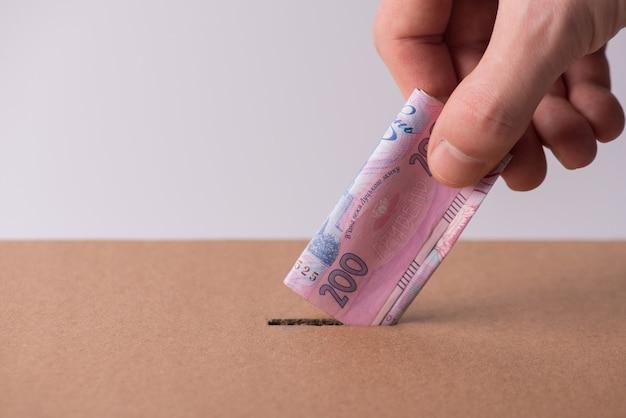 Концепция медицинского страхования. обрезанное фото крупным планом человека человеческой мужской руки, вставляющей украинские деньги в отверстие в картонной коробке