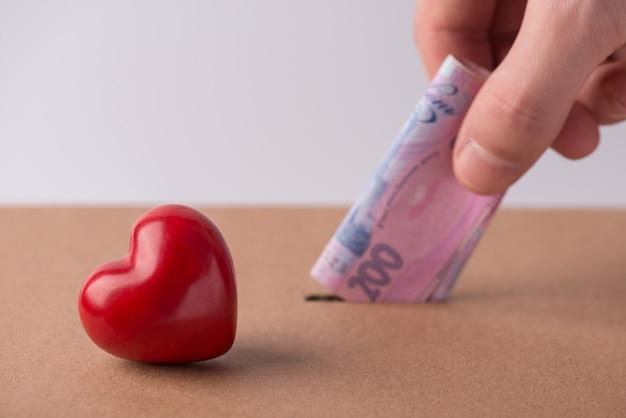 医療保険の概念。段ボール箱の穴にウクライナのお金を入れている男性人間男性の手のトリミングされたクローズアップ写真