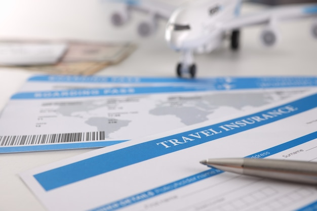 Medical insurance contract for tourists pen and plane on table. medical treatment on vacation concept