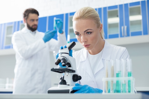 의료 실험실. 의료 실험실에서 작업하는 동안 테이블에 앉아 현미경을 들여다보고 심각한 지능형 여성 생물 학자