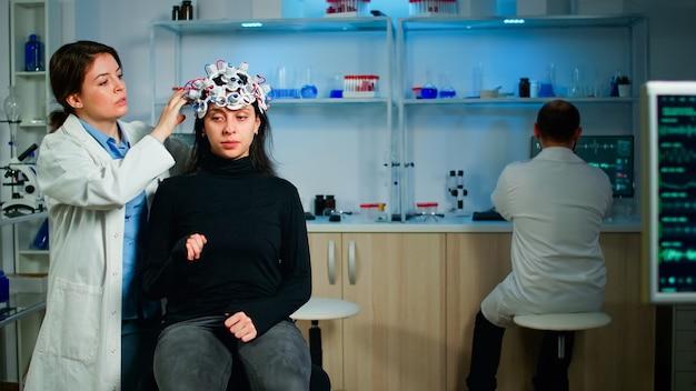 Техник медицинской лаборатории настраивает гарнитуру eeg, отслеживая функции мозга, обнаруживая диагноз