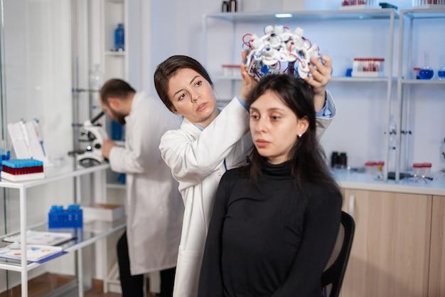 Техник медицинской лаборатории надевает гарнитуру eeg, контролирующую функции мозга, обнаруживая диагноз. команда ученых-исследователей работает поздно ночью в неврологической клинике женского здоровья.