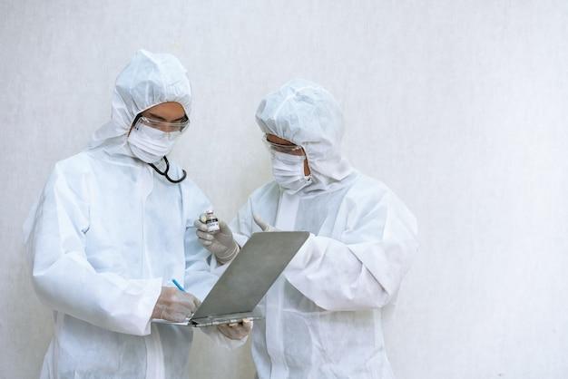 実験室でcovid-19ワクチンコロナウイルスを保持している化学防護服を着ている医療検査技師